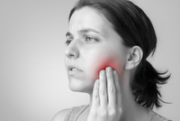 Woman holding jaw in pain due to wisdom teeth needing extraction